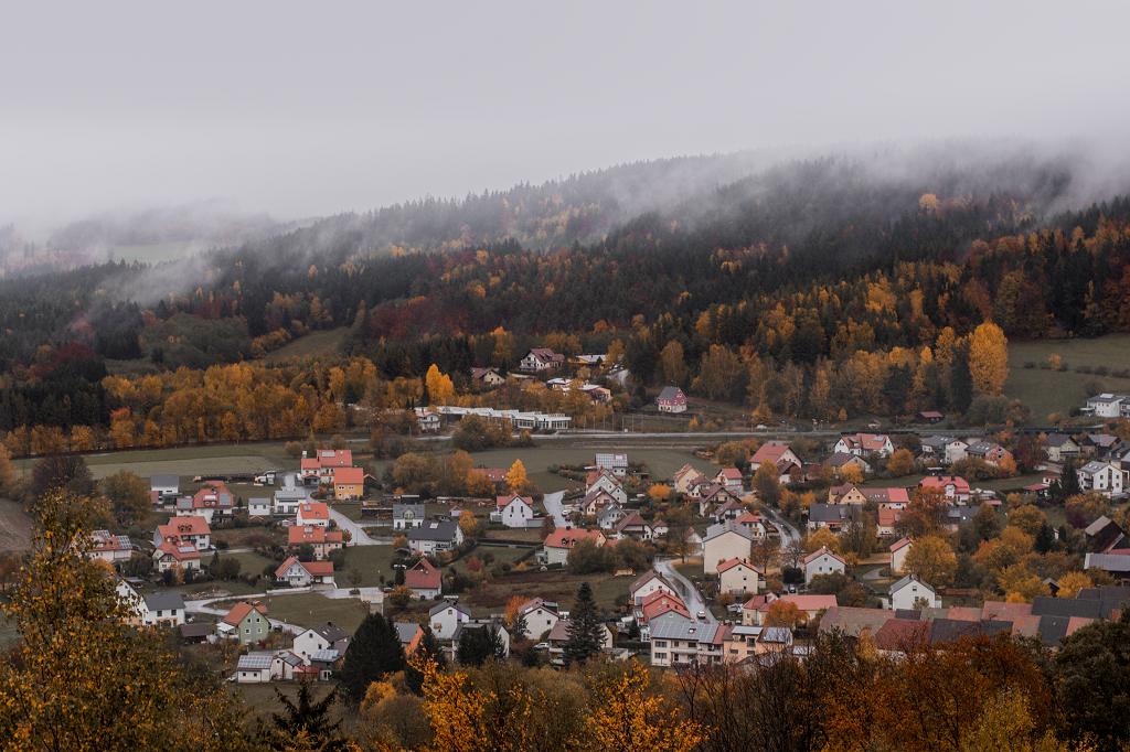 Blick auf Dorf zwischen buntem Wald
